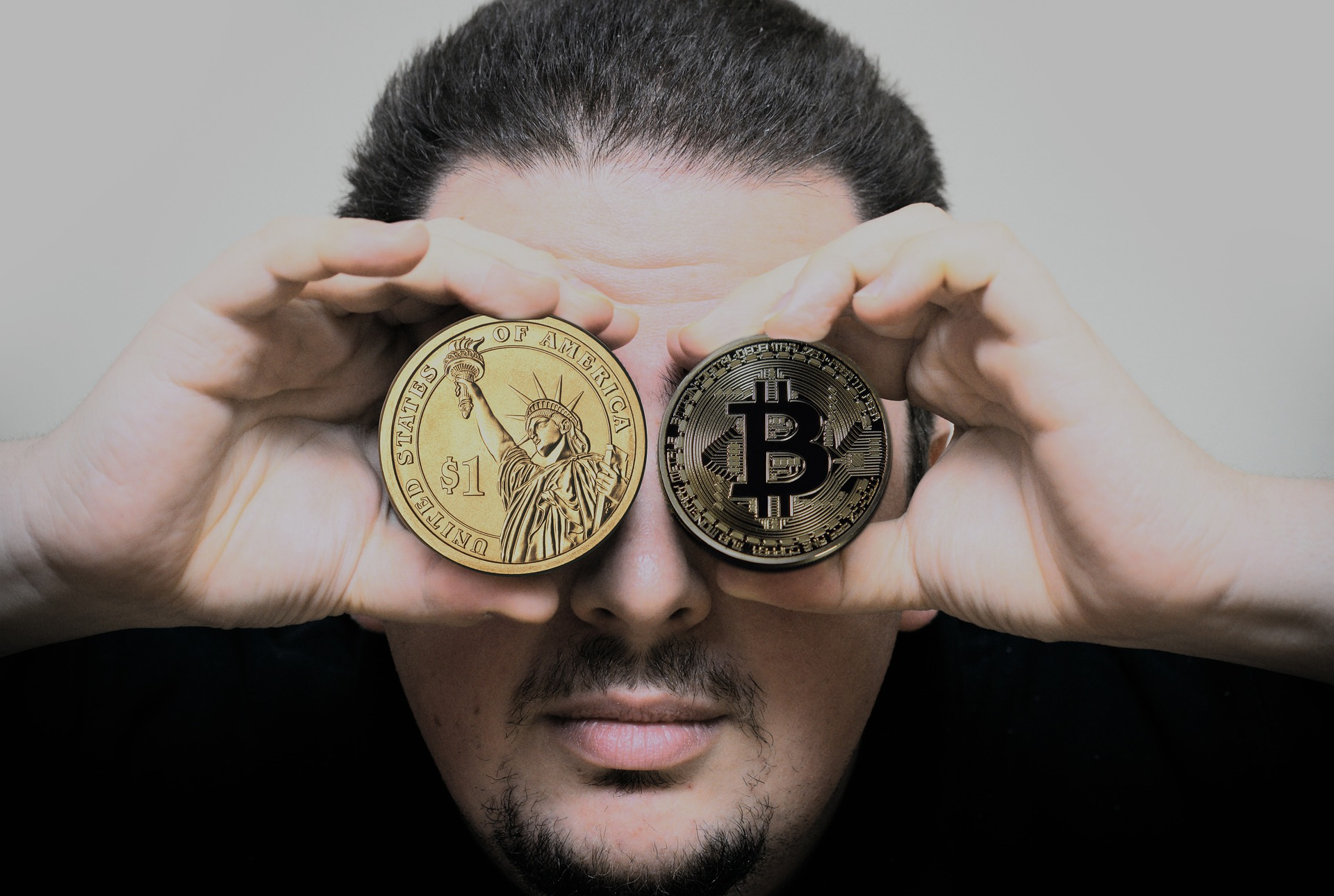 Man holding dollar, bitcoin, coin in eyes